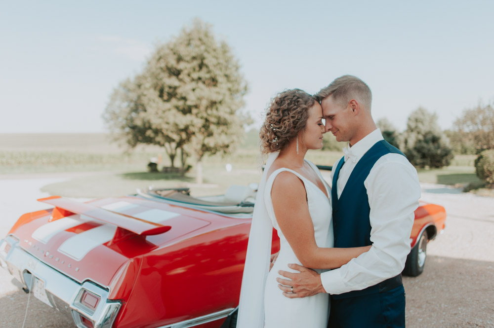 bride and groom portraits with vintage red car for wedding ceremony in pickerell-lincoln nebraska