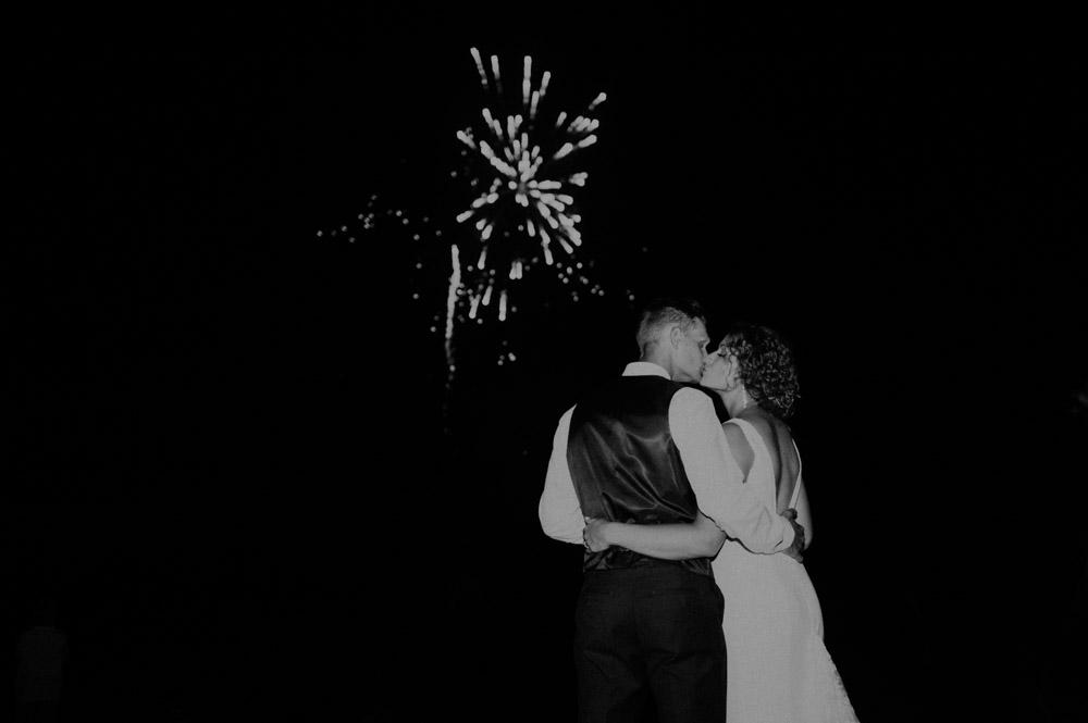bride and groom kissing under firewworks at barn wedding in pickrell-lincoln nebraska