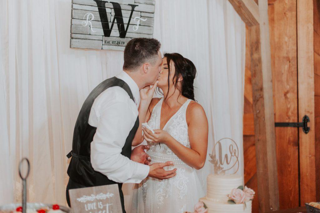 bride and groom cake cutting at ackerhurst barn in omaha, nebraska
