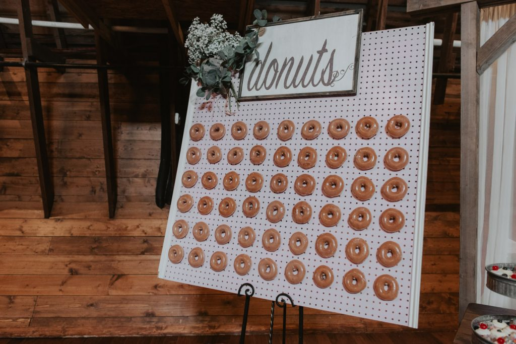 donut wall at dessert table from ackerhurst barn wedding in omaha, nebraska