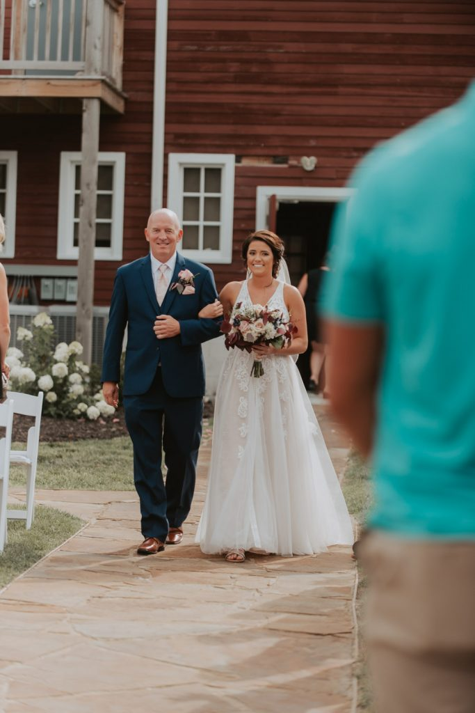 father daughter walking down the aisle wedding ceremony at ackerhurst barn in omaha, nebraska