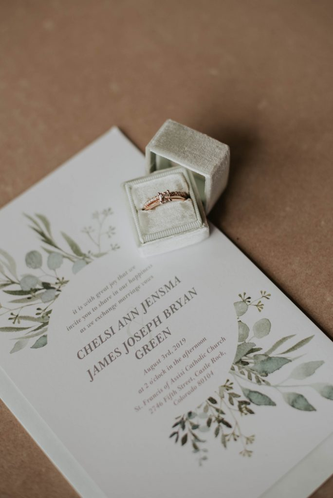 wedding invite and rings from wedding ceremony at st. francis of assisi in castle rock colorado