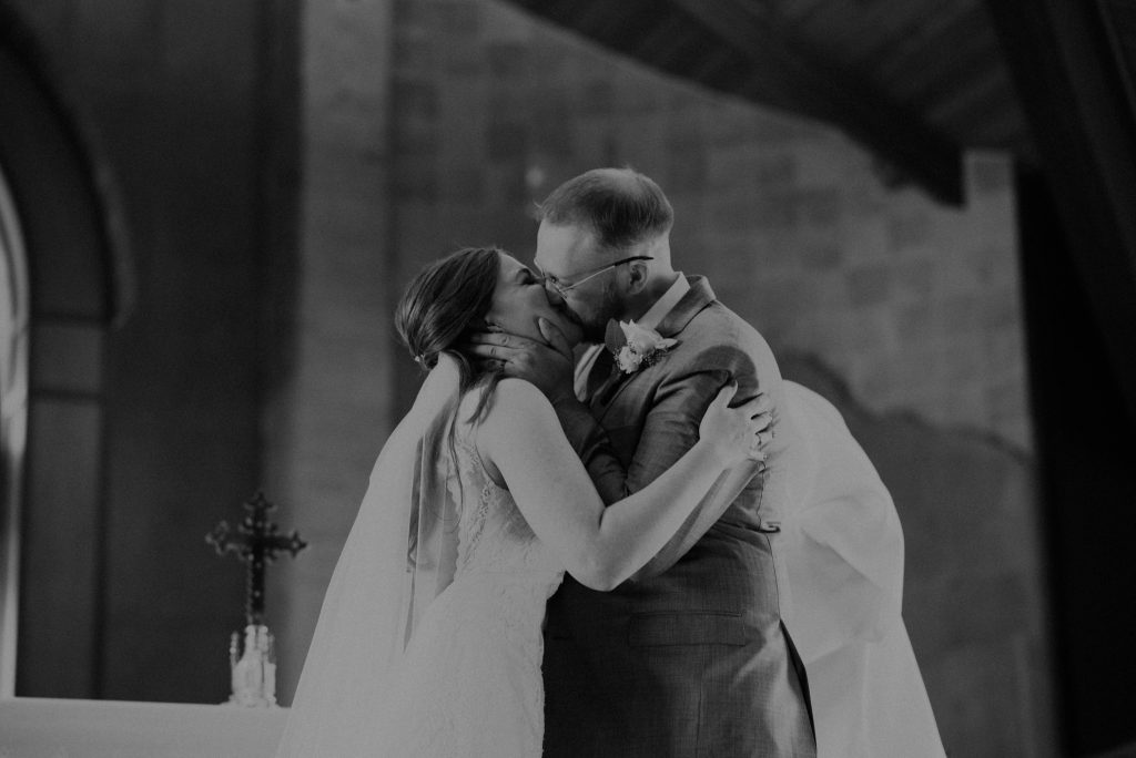 bride and groom first kiss from wedding ceremony at st. francis of assisi in castle rock colorado