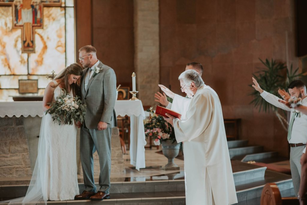 bride and groom at altar from wedding ceremony at st. francis of assisi in castle rock colorado