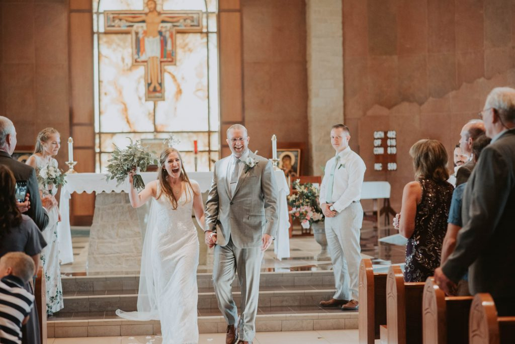 bride and groom walking off aisle from wedding ceremony at st. francis of assisi in castle rock colorado